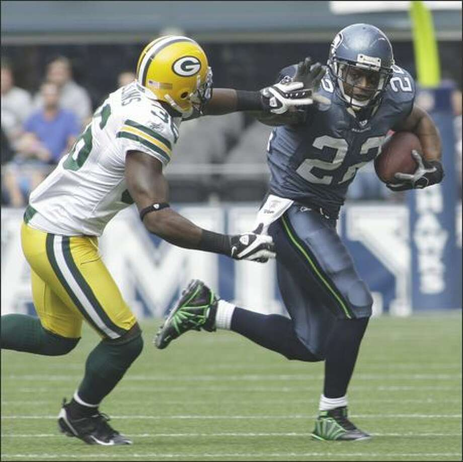 Seattle Seahawks running back Julius Jones, right, gets past Green Bay Packers safety Nick Collins, left, as he rushes in the second quarter of the football game on Sunday in Seattle. Photo: Associated Press / Associated Press