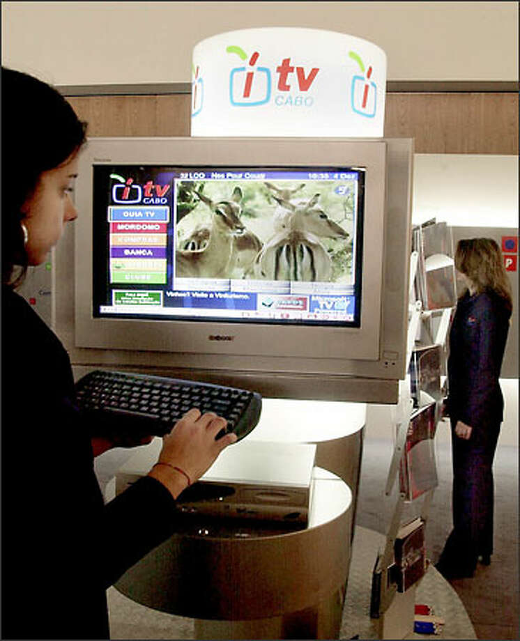 A woman in Lisbon, Portugal, tries Microsoft's interactive television service. Photo: Associated Press / Associated Press