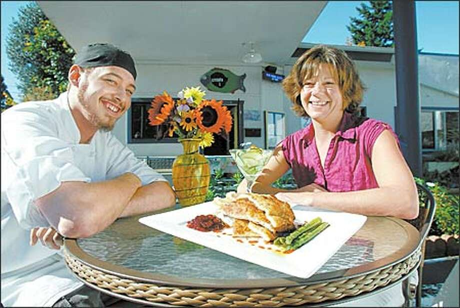 Blue Onion Bistro chef Matt Urban and co-owner Cora Leitner offer one their new items, pork schnitzel. The innovative new offerings are a best bet at the bistro. Photo: Paul Joseph Brown, Seattle Post-Intelligencer / Seattle Post-Intelligencer