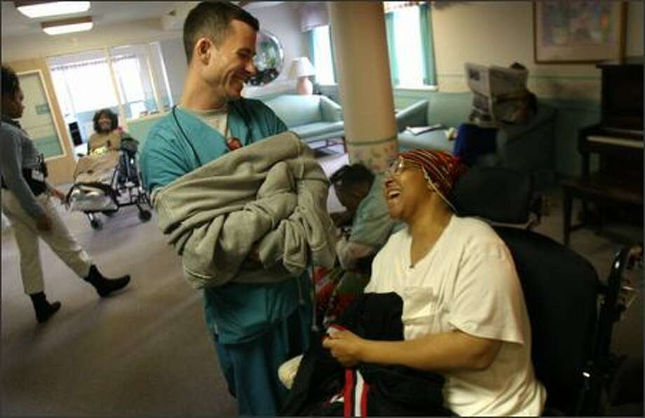 Aide Ryan Haase and resident Cheryl Hawkins laugh together at the Leon Sullivan Health Care Center in Seattle, where about half of the 146 residents would need help getting out in a disaster. Residents of scores of other facilities in the region also would need assistance. Photo: Joshua Trujillo, Seattlepi.com / seattlepi.com