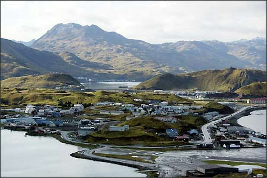 A view of Dutch Harbor, foreground, and Unalaska, Alaska, island in background, as seen from Ballyhoo Mountain. Dutch Harbor is the port from which most of the Bering Sea crab fleet operates out of before and after crab seasons. The Coast Guard says the trip out to the crab fishing grounds on Bristol Bay northeast of Dutch Harbor often is the most dangerous portion of the trip. Photo: Karen Ducey, Seattle Post-Intelligencer / Seattle Post-Intelligencer