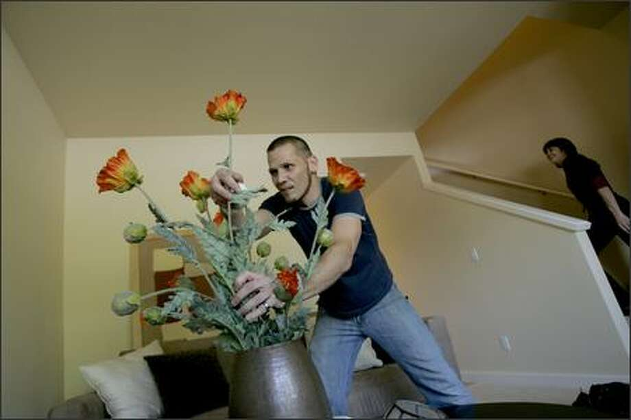 Designer Eric Ingram of Jan Sewell Design arranges decorative flowers in the living room while staging a new home in the new Rainier Vista subdivision in south Seattle on Friday. Photo: Mike Kane, Seattle Post-Intelligencer / Seattle Post-Intelligencer
