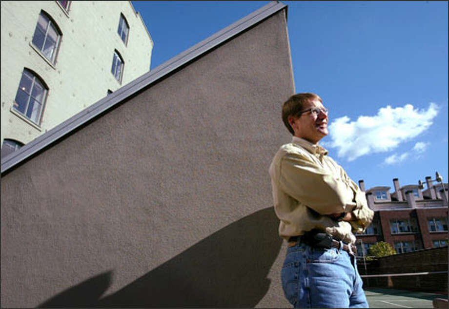"Will Hodgman, co-founder of M:Metrics, takes a break outside his Pioneer Square office last Tuesday. ""There are more people with phones in this world than any other medium,"" he says, explaining the success of his business measuring data involving cell phone use. Photo: Paul Joseph Brown, Seattle Post-Intelligencer / Seattle Post-Intelligencer"
