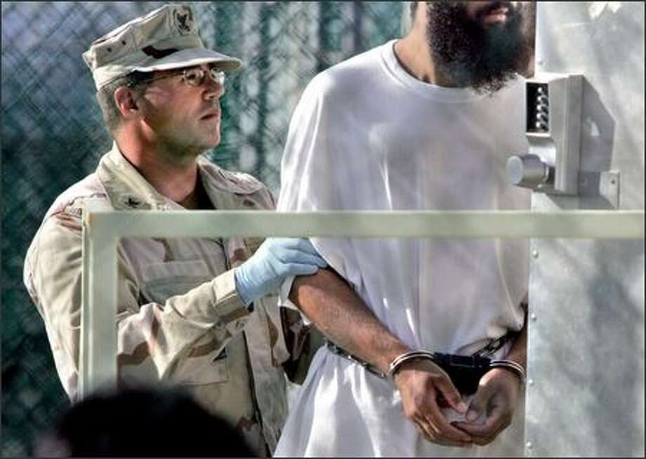 In this April 5 photograph, reviewed by a Department of Defense official, a shackled detainee is transported at Camp Delta detention facility at Guantanamo Bay in Cuba. Photo: Associated Press / Associated Press