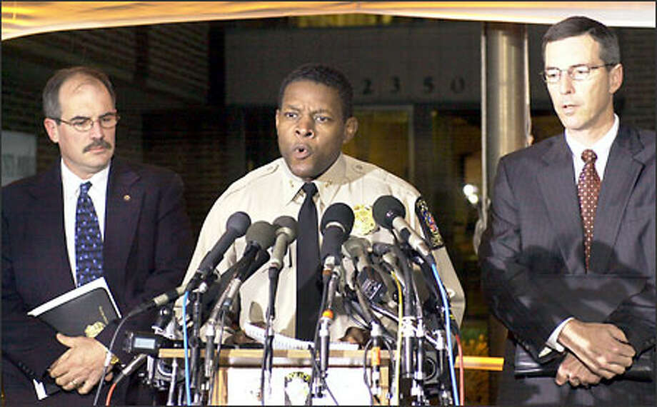 Montgomery County Police Chief Charles A. Moose, center, reads a message to the media, asking the individual who left the police a message Saturday night to contact law enforcement, as Special Agent in charge Michael Bouchard, left, of the Bureau of Alcohol Tobacco and Firearms, and FBI Special Agent in charge Gary Bald, look on. Photo: Associated Press / Associated Press