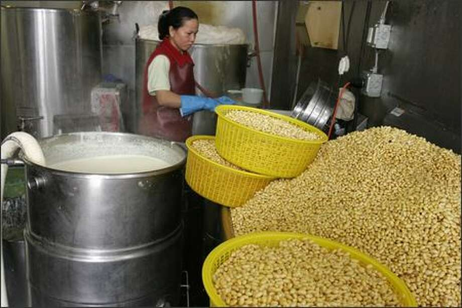 Washed soybeans wait to be ground into a slurry at the Chuminh Tofu Factory in Seattle.  The slurry -- shown in the metal container at left -- will be spun in a centrifuge to extract soy milk and okara, a fiber-rich byproduct that can be eaten by people or fed to livestock. In the background is Thuy Pham. Photo: Meryl Schenker, Seattle Post-Intelligencer / Seattle Post-Intelligencer