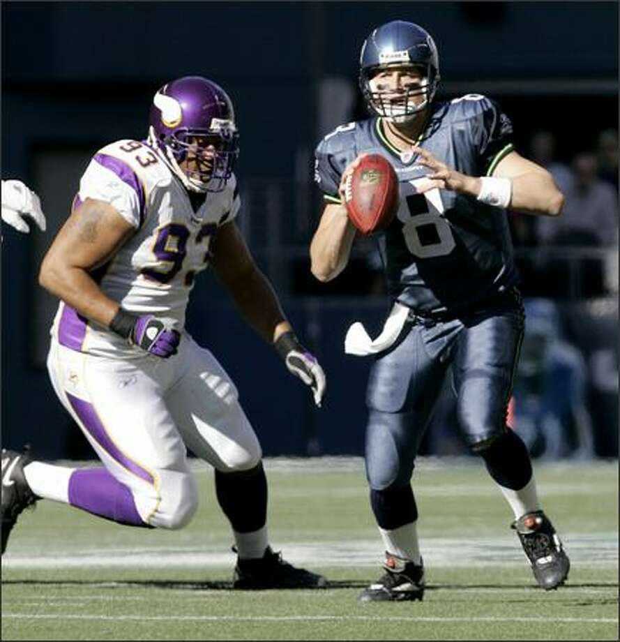 Seattle Seahawks quarterback Matt Hasselbeck, right, looks to pass as Minnesota Vikings tackle Kevin Williams closes in during the first half, Sunday at Qwest Field in Seattle. (AP Photo/Ted S. Warren)