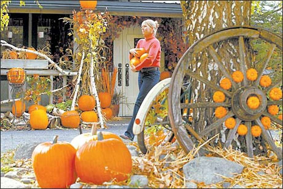 Floral designer Patti Bosket uses as many pumpkins as possible in fall decorating schemes. Here at Run of the River inn in Leavenworth, she places about 1,200 around the property. Photo: Grant M. Haller, Seattle Post-Intelligencer / Seattle Post-Intelligencer