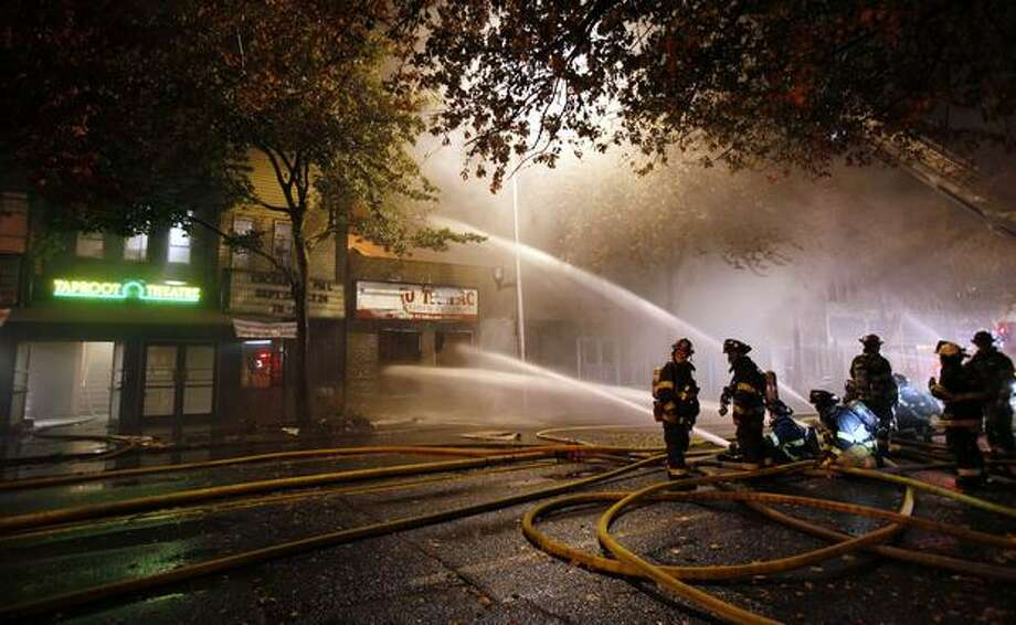 Firefighters pour water on a three-alarm fire burning in a commercial building in Seattle's Greenwood neighborhood early Friday morning. (AP Photo/Elaine Thompson) Photo: Associated Press / Associated Press