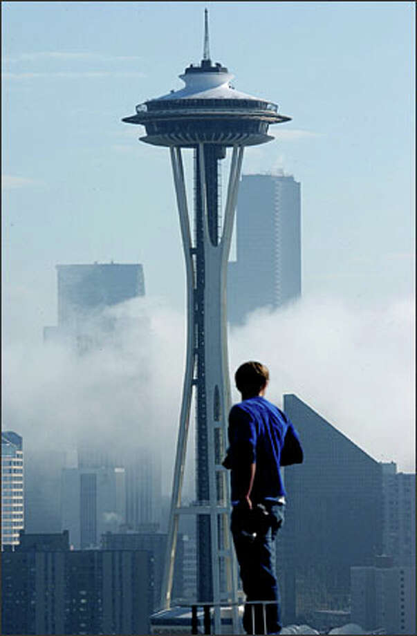 Steve Machuga is well-armed with a still camera and a video camera, but has to wait for the light to improve as a big fog bank rolls over the city of Seattle. Machuga was photographing the Space Needle yesterday. The interruption was brief, as the fog quietly rolled away. Photo: Jeff Larsen, Seattle Post-Intelligencer / Seattle Post-Intelligencer