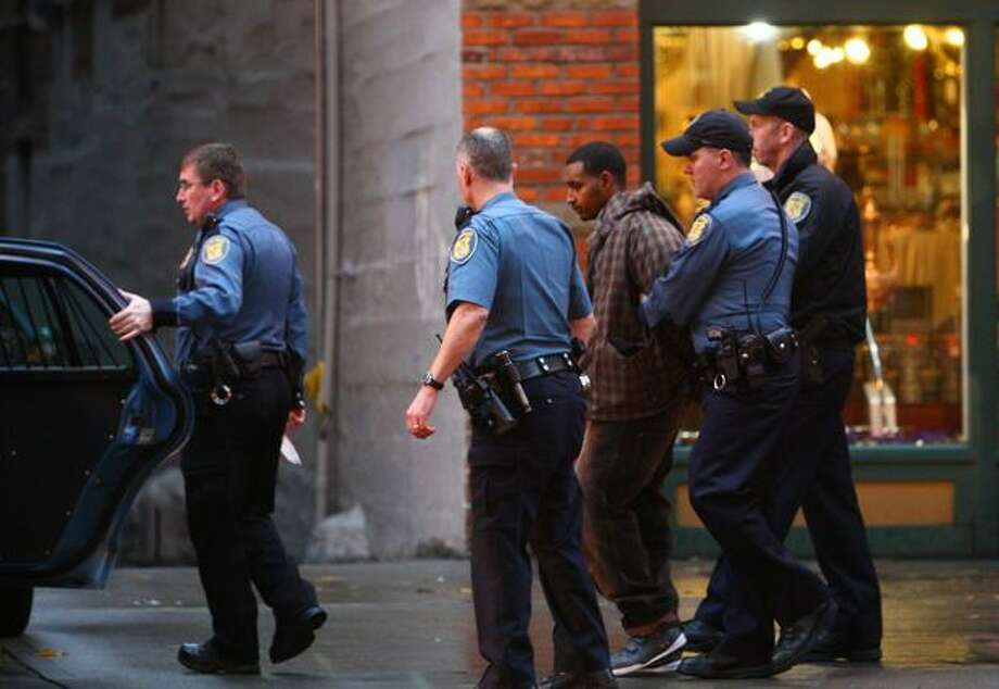 A man police described as a suspect is detained after a man was shot in the head at the intersection of Second Avenue and Pike Street in downtown Seattle on Tuesday, October 26, 2010. A gun was also found nearby after the man fled down an alley. Photo: Joshua Trujillo, Seattlepi.com / seattlepi.com