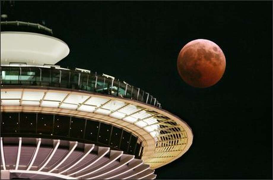 The full moon turns red and orange as it passes the Space Needle during a total lunar eclipse. (AP Photo/Elaine Thompson) Photo: Associated Press / Associated Press