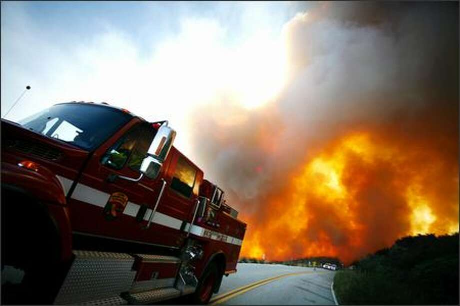 Due to heavy winds, a California Department of Forestry fire engine is positioned away from a wildfire as it jumps Highway 243 in Banning, Calif., on Thursday. Photo: Associated Press / Associated Press