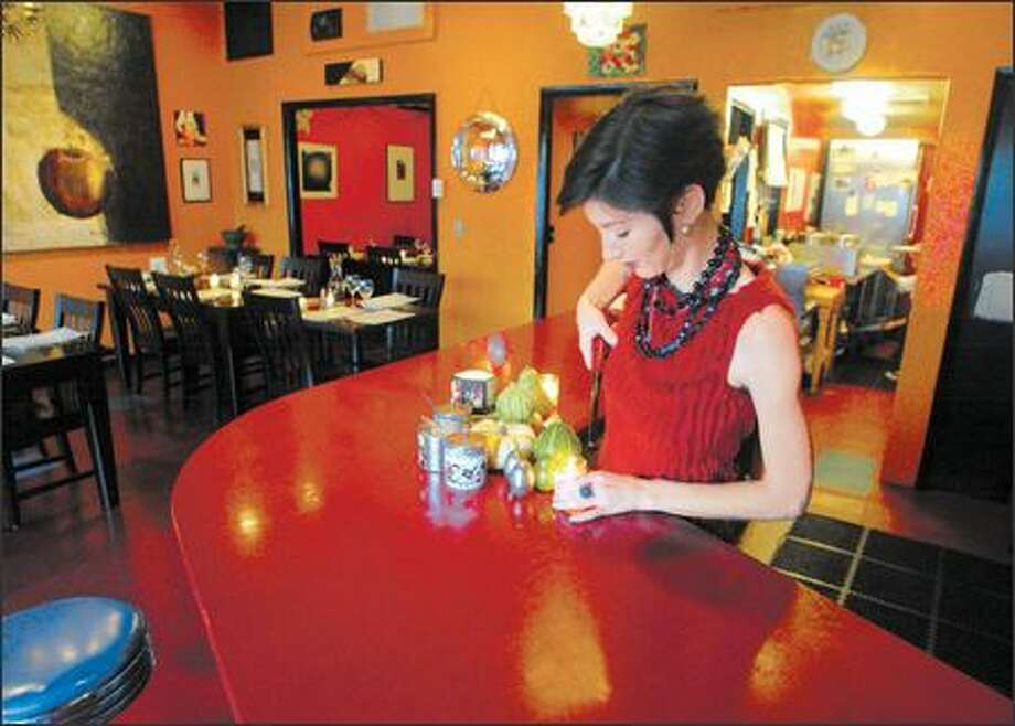 Waitperson Gretchen Bone lights candles at Persimmon. The cozy restaurant hasn't had a high profile but it has added dinner service, which should help its visibility. Photo: Gilbert W. Arias, Seattle Post-Intelligencer / Seattle Post-Intelligencer