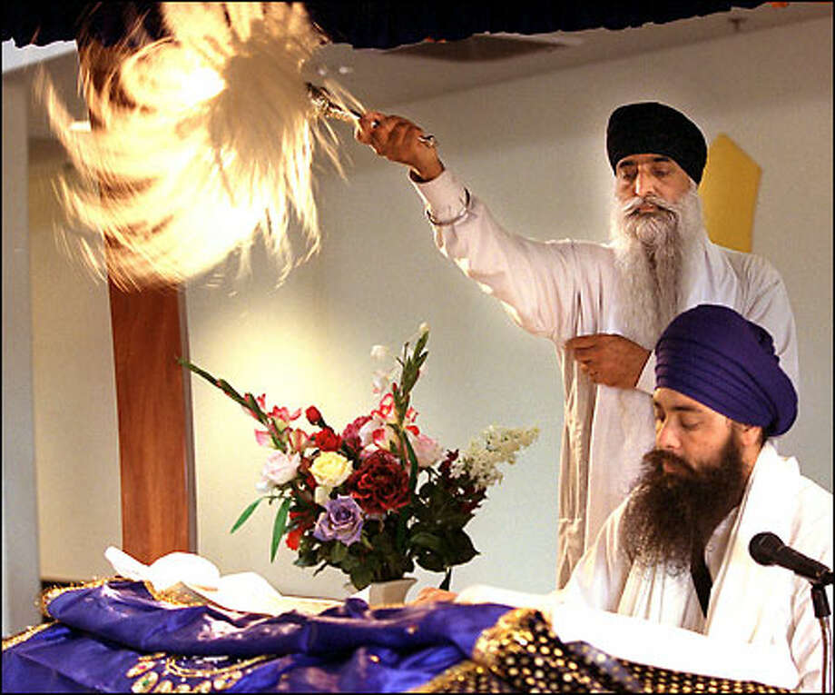 "Joginder Singh reads from the holy book as Jarniel Singh waves a chauri, made from feathers or hair, in respect for ""The Word"" of the guru. Sikhs are followers of 10 gurus, or prophets. Photo: Renee C. Byer, Seattle Post-Intelligencer / Seattle Post-Intelligencer"