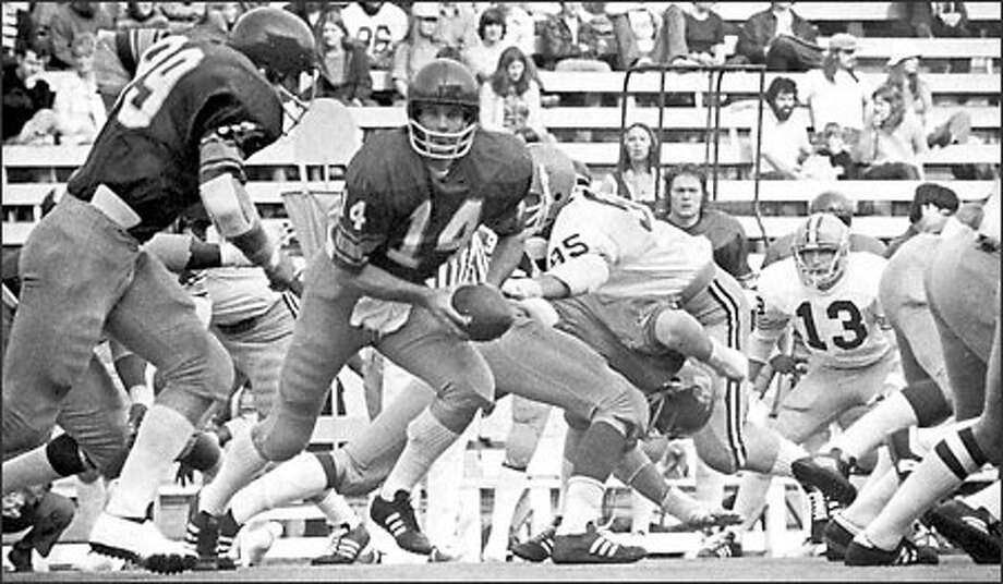 Huskies quarterback Dennis Fitzpatick hands off to fullback Robin Earl in Washington's 66-0 victory over Oregon in 1974, avenging a 58-0 Ducks victory the year before and completing a 124-point swing. Photo: Grant M. Haller, Seattle Post-Intelligencer / Seattle Post-Intelligencer