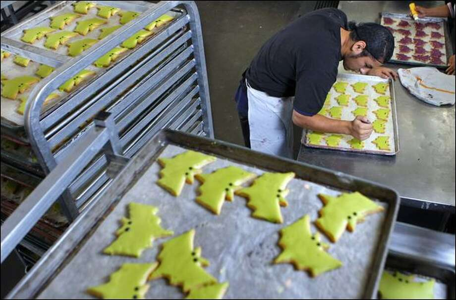 Jose Valenzuela decorates Halloween cookies at Little Rae's Bakery, which made its employees promise not to bring products with nuts into the building. (Andy Rogers / Seattle Post-intelligencer Photos)