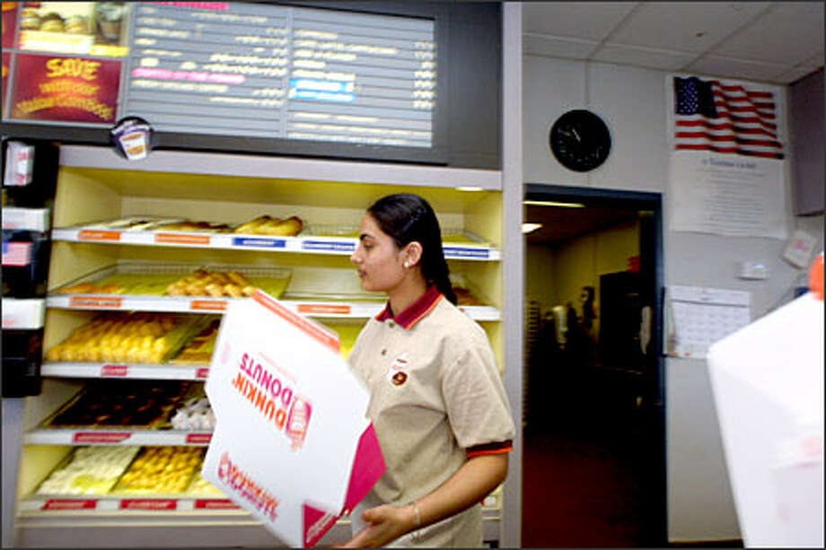 Lakhwinder Kaur works at the Dunkin' Donuts in Burien, one of two remaining Dunkin' Donuts shops in the state. The shop will stay in business under the name Cafe Donuts. Photo: Phil H. Webber, Seattle Post-Intelligencer / Seattle Post-Intelligencer
