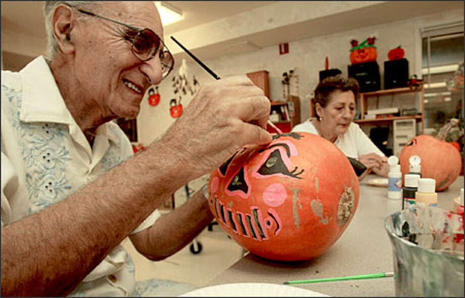 Daniel Cavallo, left, and Betty McLaughlin paint pumpkins at Seabrook Assisted Living in Everett as the center prepares for trick-or-treating children. Photo: Grant M. Haller, Seattle Post-Intelligencer / Seattle Post-Intelligencer