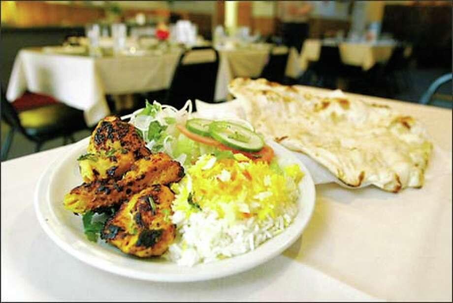 Ordering karahi at BBQ Hut brings the Pakistani version of wok-cooking, which is drier than curries. It's accompanied above by rice and naan -- a tandoor-oven baked bread. Photo: Joshua Trujillo, Seattlepi.com / seattlepi.com