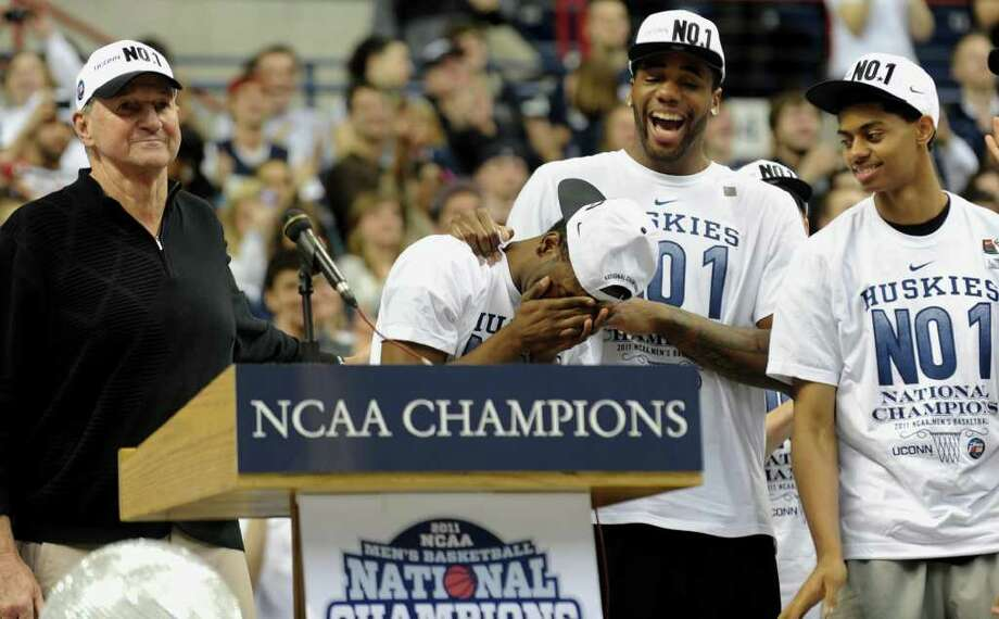 UCONN's Kemba Walker is overcome with emotion as his number is unveiled on the wall during a rally held for the men's basketball team at Gampel Pavilion in Storrs, Conn. on Friday April 5, 2011. With Walker on stage is Head Coach Jim Calhoun, left, and teammates Alex Oriakhi and Jeremy Lamb, at right. Photo: Christian Abraham / Connecticut Post