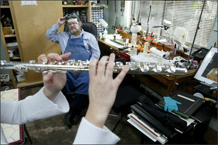 Alexander Eppler takes a moment from work to listen as apprentice Danijela Djakovic tests a flute at the Seattle shop on Friday. Djakovic, who is also a flute instructor and owns a silver instrument made by Eppler, plays in the Lake Union Civic Orchestra. She calls Eppler a demanding teacher. Photo: Mike Urban, Seattle Post-Intelligencer / Seattle Post-Intelligencer
