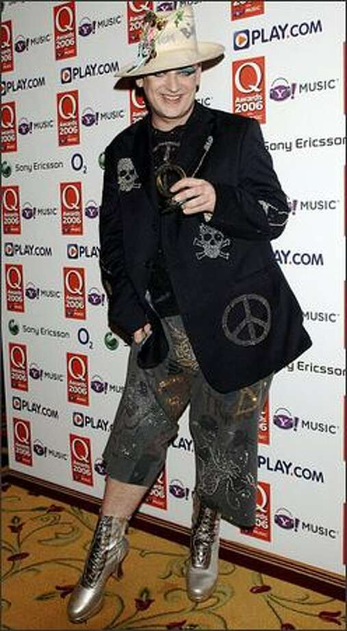 "Boy George displays his Q Classic Song award -- for Culture Club's ""Karma Chameleon"" -- at Q magazine's Q Awards ceremony Monday in London. Boy George, who swept New York's streets in August as punishment for falsely reporting a burglary, said, ""I'm so glad to get this award because it means you now recognize me again as a singer and not a road sweeper."" Photo: Associated Press / Associated Press"