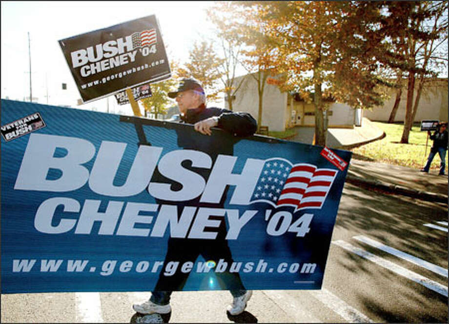 Warren Peterson crosses Fifth Avenue Northeast after waving signs for two hours at the corner of Fifth and Northgate Way. Some drivers are rude to Peterson, but that doesn't discourage him from trying to get Bush a few more votes. Photo: Meryl Schenker, Seattle Post-Intelligencer / Seattle Post-Intelligencer