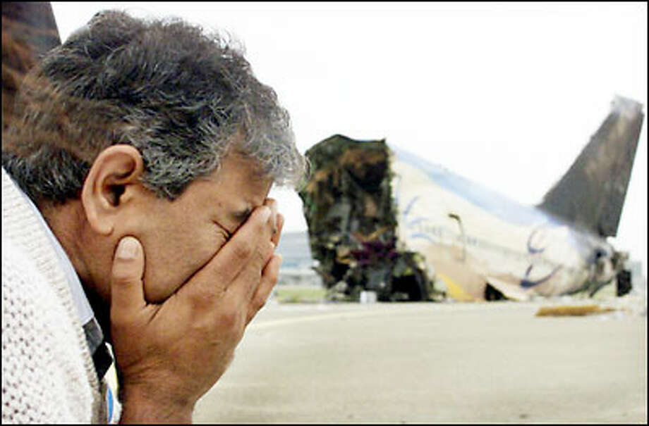 An unidentified relative of a victim of the Singapore Airways crash weeps as he views the wreckage of the Boeing 747 that crashed Tuesday during takeoff at an airport in Taipei. Eighty-one people died when the pilot got onto the wrong runway and collided with construction equipment. Photo: Associated Press / Associated Press