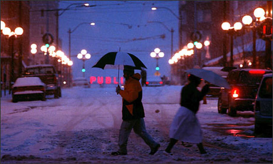 Pedestrians cross Pine Street near Westlake Center as snow falls. Photo: Scott Eklund, Seattle Post-Intelligencer / Seattle Post-Intelligencer