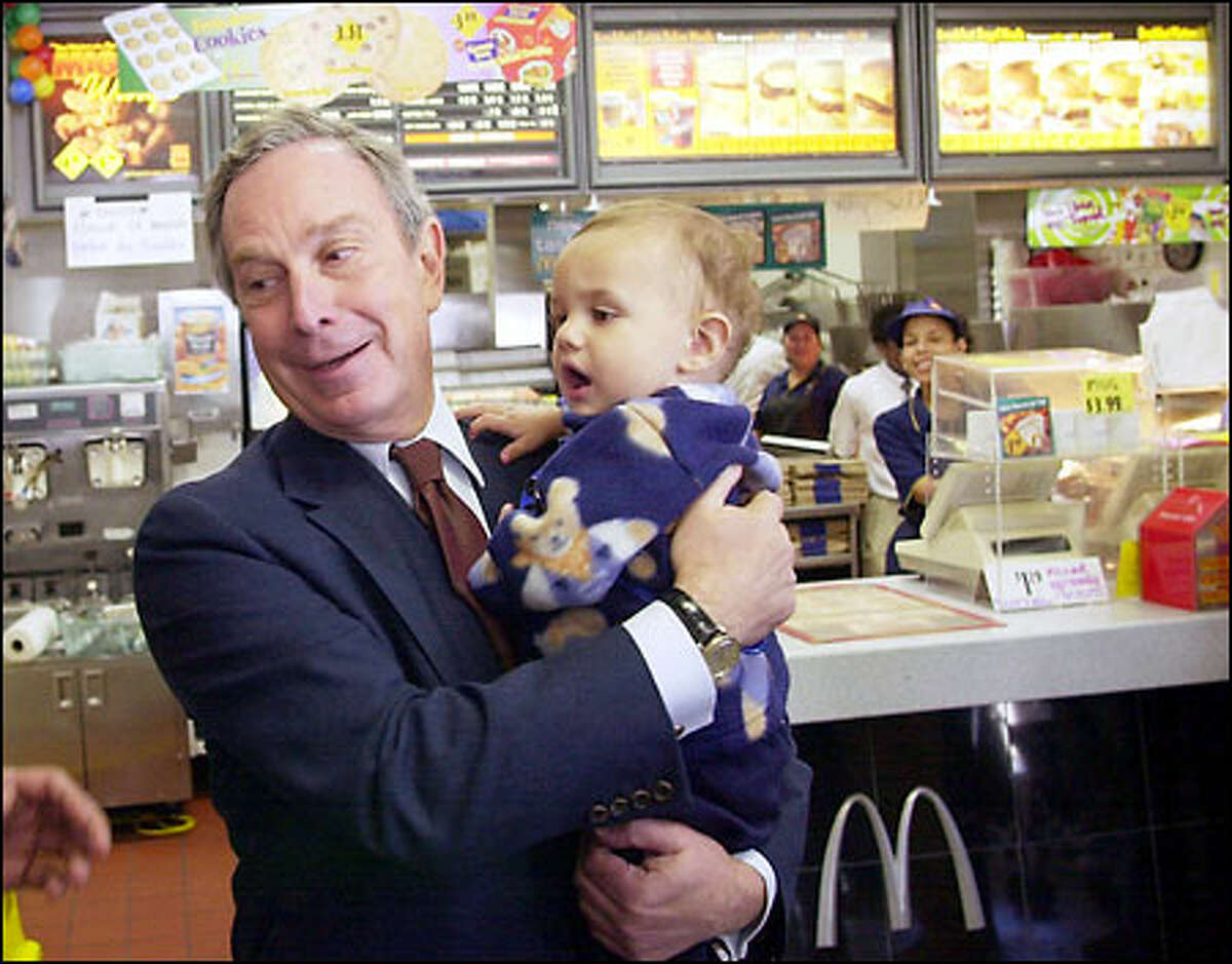 Michael Bloomberg campaigned as a Republican for Mayor of New York. He is now running for President as a Democrat. Here, he holds 11-month-old Joshua Rodriguez, during an impromptu stop at a Brooklyn fast-food restaurant. He spent $40 million to get elected mayor.