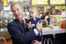 Michael Bloomberg, Republican candidate for New York mayor, holds 11-month-old Joshua Rodriguez, during an impromptu stop at a Brooklyn fast-food restaurant. Bloomberg's campaign has cost him more than $40 million.