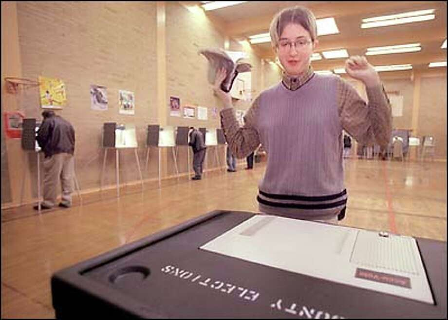 Angi Porch, who turned 18 on Election Day, inserts her first-ever completed ballot into a ballot box in the gym at Madrona Elementary Tuesday.  She read her voters' guide until it became tattered, and hopes to one day become governor. Photo: Melina Mara, Seattle Post-Intelligencer / Seattle Post-Intelligencer