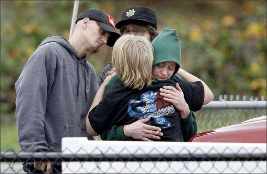 Dori Beaupre (center) hugs her son Colter, 11, near the scene where a car carrying Beaupre's 2-year-old son Hunter plunged into the Green River in Auburn on Friday. At left is Chad Beaupre, Hunter's father. Rescue personnel suspended the recovery of car, believed to still contain the 2-year-old and a 13-year-old, because of the danger to personnel. A 16-year-old driving the car escaped after the car skidded into the river. Photo: Dan DeLong, Seattle Post-Intelligencer / Seattle Post-Intelligencer