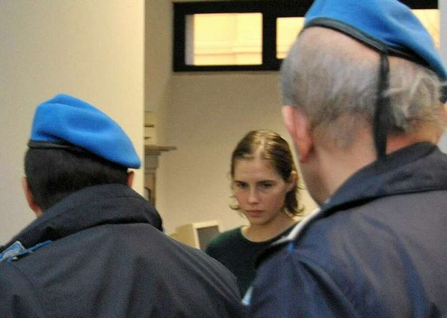 Amanda Knox, center, is escorted by penitentiary police officers after a hearing in Perugia, Italy, where a judge ordered her to stand trial on slander charges for claiming she was beaten by police when questioned in 2007 about her roommate's slaying. The 23-year-old American maintains she was just trying to defend herself and never meant any offense or to slander anybody, her lawyers said. Knox is serving a 26-year prison term after she was convicted of murdering her roommate Meredith Kercher. (AP Photo/Stefano Medici) Photo: Associated Press / Associated Press