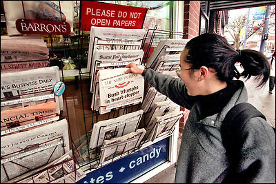 Joy Andrada laughs as she reads the headline in Tacoma's The News Tribune yesterday at the Broadway News stand. Photo: Grant M. Haller, Seattle Post-Intelligencer / Seattle Post-Intelligencer