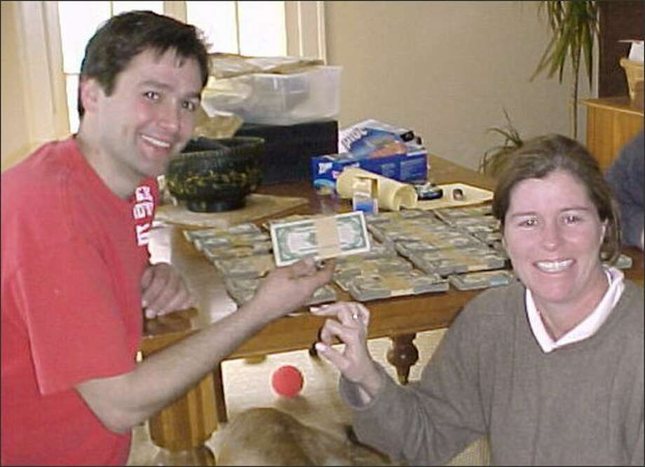 Contractor Bob Kitts, left, and homeowner Amanda Reece pose with money found at Reece's home in Cleveland. The discovery amounted to little more than grief for Kitts, who couldn't agree on how to split the money with Reece. (Bob Kitts photo via AP) Photo: Associated Press / Associated Press