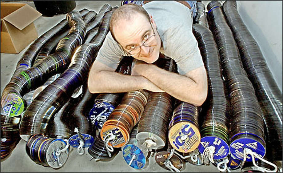 John Lieberman poses with thousands of America Online promotional compact disks at his home in El Cerrito, Calif., Friday, Nov. 8, 2002. Lieberman and Jim McKenna are asking anyone and everyone to send their unwanted CDs to them and once they get a million they're driving them to AOL headquarters in Virginia and asking them to politely stop.  Armed with their Web site, the two have collected over 80,000 of the disks, which offer trial subscriptions to AOL's services. (AP Photo/Paul Sakuma) Photo: Associated Press / Associated Press