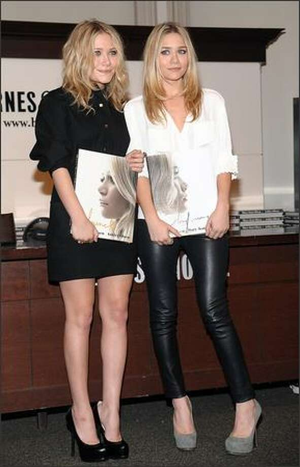 "Mary-Kate Olsen, left, and Ashley attend a book signing to promote their new book ""Influence"" in New York. Photo: Associated Press / Associated Press"