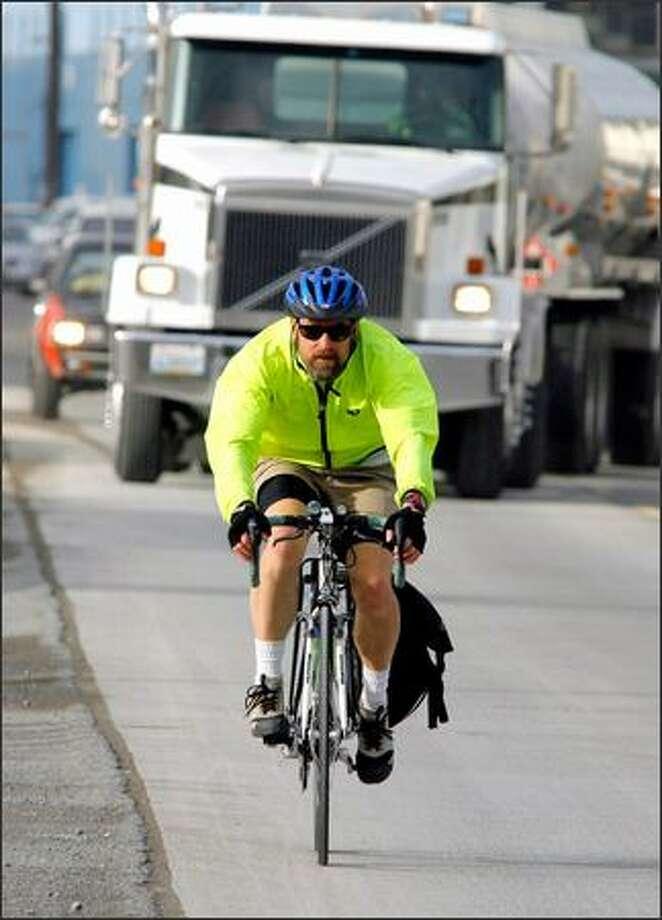"Cyclist John Higgins navigates through heavy traffic as he rides down Shilshole Avenue in Ballard, part of the ""missing link"" of the Burke-Gilman Trail. The 1.4-mile gap travels through an industrial area of Ballard. Photo: Gilbert W. Arias, Seattle Post-Intelligencer / Seattle Post-Intelligencer"