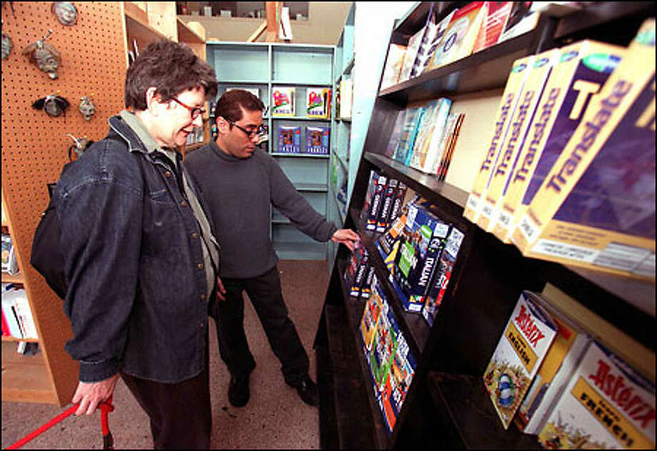 Preparing for a trip to Italy, Alberta Weinberg chats with sales agent Paul Torres at the Multilingualbooks.com store on East Pike, where a big seller these troubled days is Arabic. Photo: Phil H. Webber, Seattle Post-Intelligencer / Seattle Post-Intelligencer