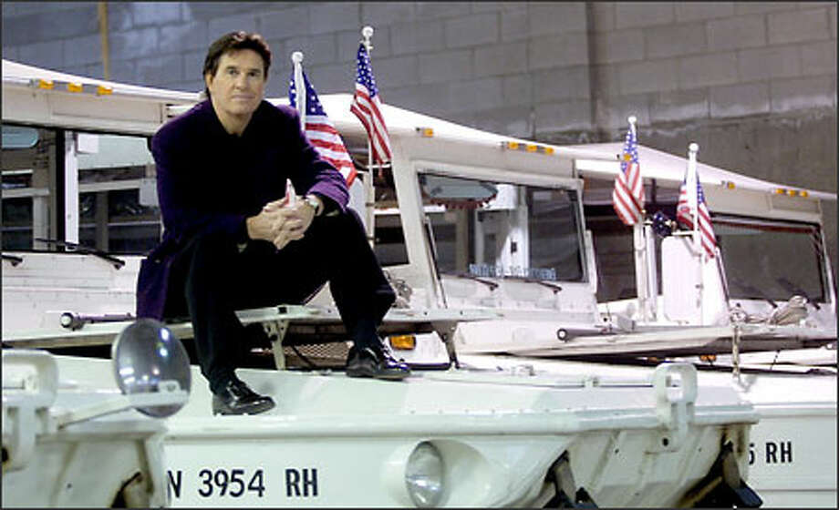 "Brian Tracey, owner of Ride the Ducks, poses with several of his amphibious tour craft at his warehouse near Fremont. He said yesterday that by next spring, he will add two more craft to his five-boat fleet as the business continues to expand. The former host of the Seattle television program ""Evening Magazine"" said his company plans to add a comedy tour in January as he continues to develop his customer base. Photo: Phil H. Webber, Seattle Post-Intelligencer / Seattle Post-Intelligencer"