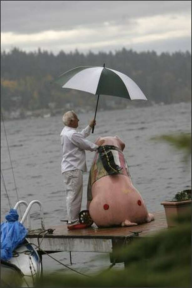 """Pete Buck shields """"In a Pig's I-5"""" from the rain on his dock on Lake Washington. Photo: Grant M. Haller, Seattle Post-Intelligencer / Seattle Post-Intelligencer"""