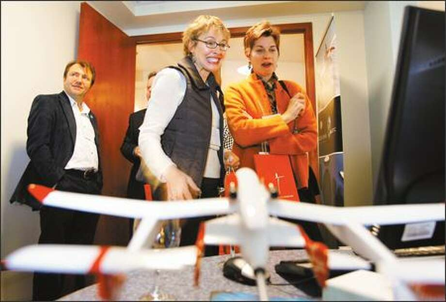 Pam Kovarik, left, and her neighbor Carol Lucas, right, discuss the possibility of space travel as they watch a video presentation by Virgin Galactic at the Tangerine Travel customer appreciation reception in Bothell on Thursday. Photo: Gilbert W. Arias, Seattle Post-Intelligencer / Seattle Post-Intelligencer
