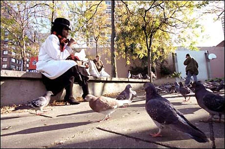 Sylvia Gillespie, a homeless woman who frequents Regrade Park at Third Avenue and Bell Street to feed the pigeons, passes the time on a cool fall day. Photo: Paul Joseph Brown, Seattle Post-Intelligencer / Seattle Post-Intelligencer