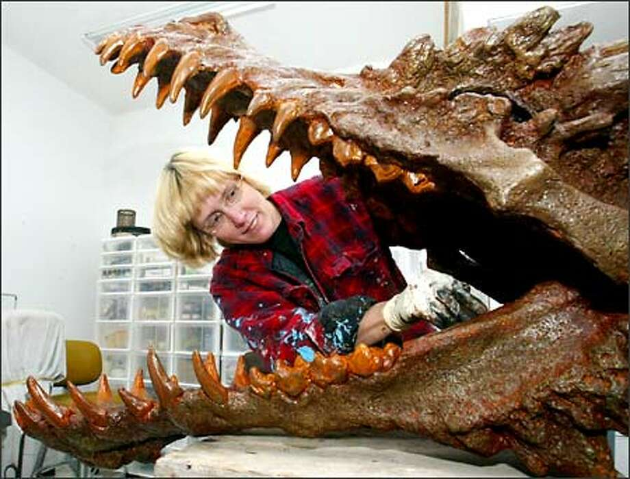 Kim Graham paints the inside of her dragon sculpture with a rusty color so it will look like a fossil. Photo: Grant M. Haller, Seattle Post-Intelligencer / Seattle Post-Intelligencer