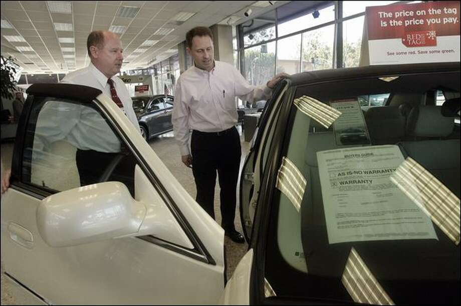 Chevrolet sales manager Tom Callahan, left, shows Edward Dollard a Cadillac DTS in a Los Angeles showroom Wednesday. Photo: Associated Press / Associated Press