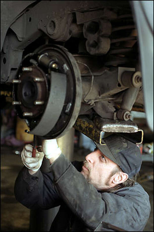 Bill Rice, a mechanic at 1st Tire and Wheel, replaces a set of brake shoes. Rice says he can't even change a tire without getting brake dust on him. He says he tries to hold his breath to avoid inhaling it. Photo: Meryl Schenker, Seattle Post-Intelligencer / Seattle Post-Intelligencer