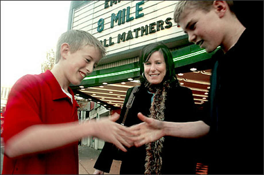 "Evan Lince, 13, left, and Kevin Vlcek, 13, demonstrate a handshake they saw in ""8-Mile."" Watching is Janet Leduc, who took the boys to see the R-rated film. The movie could ""breed some understanding of rap,"" Leduc said. Photo: Grant M. Haller, Seattle Post-Intelligencer / Seattle Post-Intelligencer"