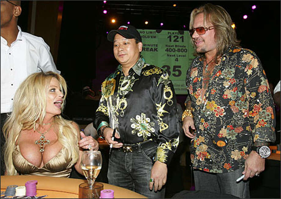 This picture screams class: Here's Vince Neil (lookin' all greasy and gross), with poker champ Johnny Chan and the missus, Lia, at the opening of Neil's Texas hold 'em poker tournament in Las Vegas. We can't help but notice that Chan is lookin' not at Mrs. Neil's chips, but at the floatation devices she has attached to her chest. (ETHAN MILLER/GETTY IMAGES) Photo: Associated Press / Associated Press